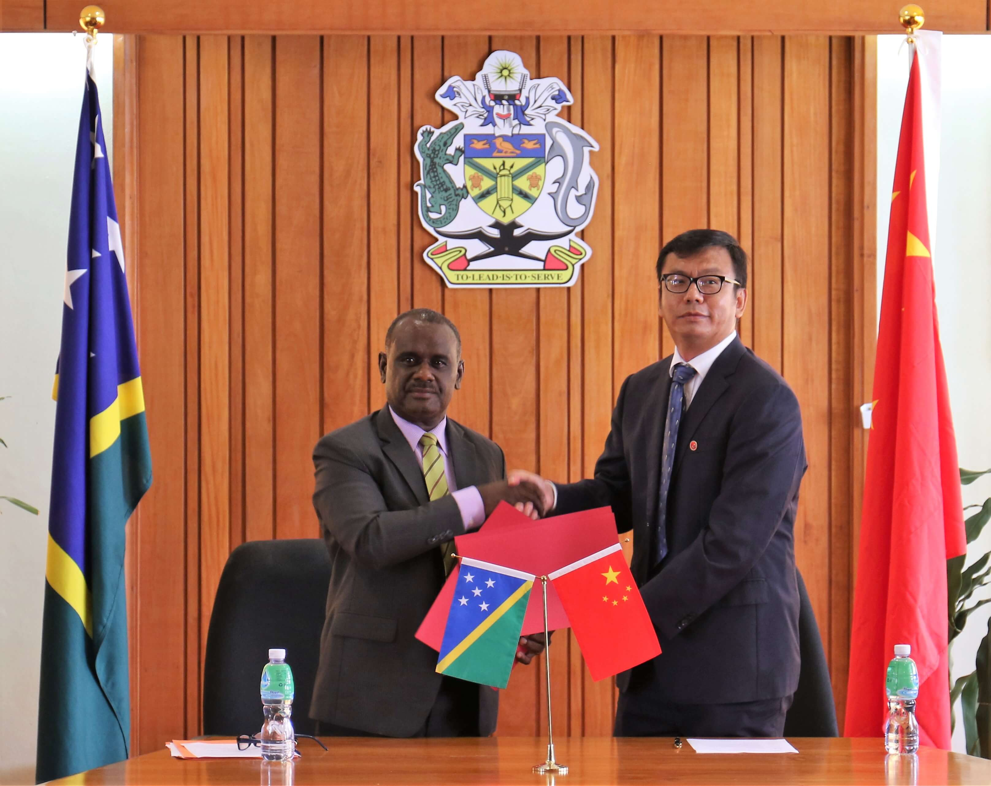 Minister Manele and PRC Chargé D'affaires Yao Ming exchanging of notes after the signing ceremony.